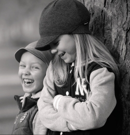 kids laughing next to a tree