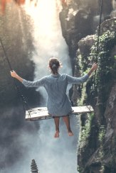 woman on swing over waterfall