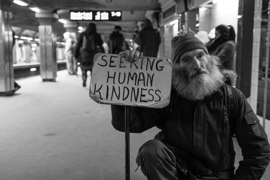 image of homeless man holding a sign that reads seeking human kindness