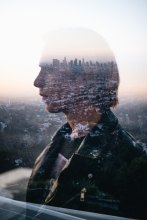 double exposure of man peering into distance over cityscape
