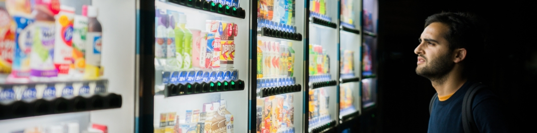 image of man staring at array of vending machines